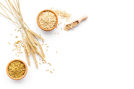Oatmeal and oat in bowls near sprigs of wheat on white background top view. Banque d'images