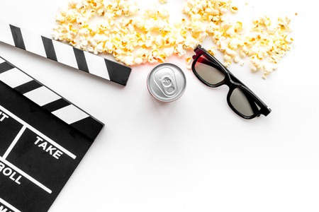 Cinema background. Film watcing. Glasses, popcorn and clapperboard on white background top view.