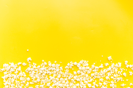 Popcorn background on yellow top view copy space