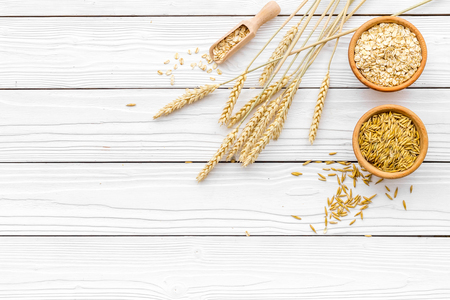Food which rich with slow carbohydrates. Oatmeal and oat in bowls near sprigs of wheat on white wooden background top view copy space