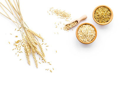 Oatmeal and oat in bowls near sprigs of wheat on white background top view copy space Standard-Bild