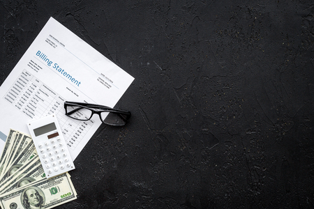 Paying bills. Billing statement near calculator, money, glasses on black background top view.