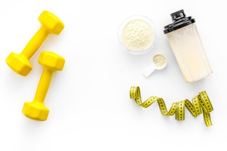 Nutrition for muscle growth. Scoop of protein near shaker and dumbbell on white background top view.