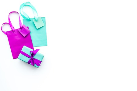 Gift box and colorful paper bag on white background top view copy space