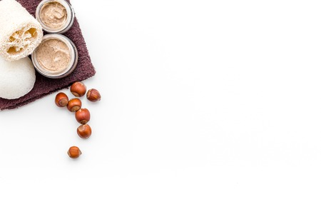 Natural cosmetics for skin care. Body scrub with hazelnut. White background top view copy space Stock Photo