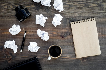 Writer profession. Retro concept. Notebook, pen, inkpot, coffee near crumpled paper balls on dark wooden background top view. Standard-Bild - 96431186