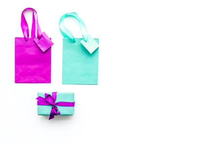 Gift box and colorful paper bag on white background top view. Reklamní fotografie