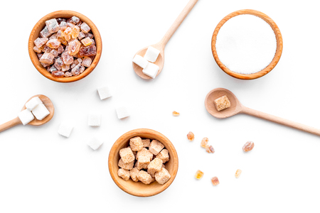 Sugar background on white. Bowls with different kinds of sugar. Top view Stock Photo