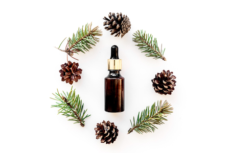 Pine essential oil in bottles on white background top view copy space. Pattern with pine branch and cone
