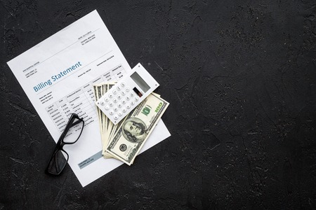 Paying bills. Billing statement near calculator, money, glasses on black background top view copy space