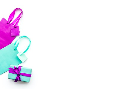 Gift box and colorful paper bag on white background top view. Reklamní fotografie - 96499681