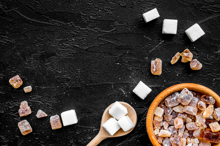 Types of sugar. Candy brown sugar in bowl and scoop on black background top view.