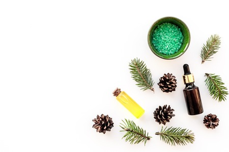 Pine spa cosmetics, products for skin care. Fir essential oil and green aromatic spa salt near branches and cones on white background top view. Stock fotó