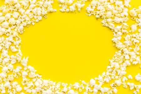 Popcorn background on yellow top view copy space. Archivio Fotografico