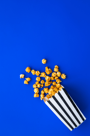 Popcorn in paper bag scattered on blue background top view.