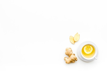 Cup of ginger tea near ginger root on white background top view. Stock Photo