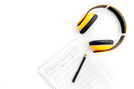 Work desk of modern composer. Music notes near headphones on white background top view copy space