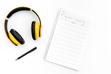 Work desk of modern composer. Music notes near headphones on white background top view