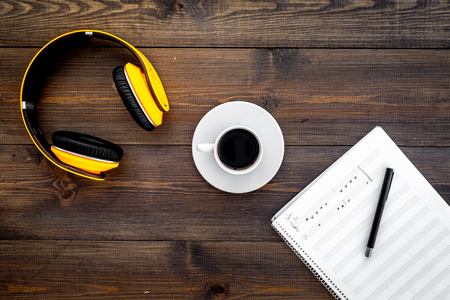 Work desk of modern composer. Music notes near headphones and coffee on dark wooden background top view copy space Stock Photo