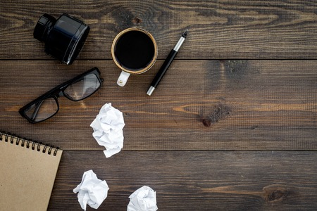 Writer profession. Retro concept. Notebook, pen, inkpot, coffee near crumpled paper balls on dark wooden background top view copy space Standard-Bild - 96711283