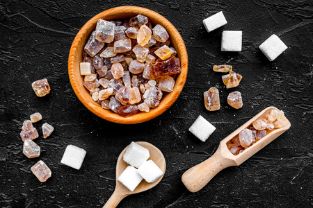 Types of sugar. Candy brown sugar in bowl and scoop on black background top view Stock Photo