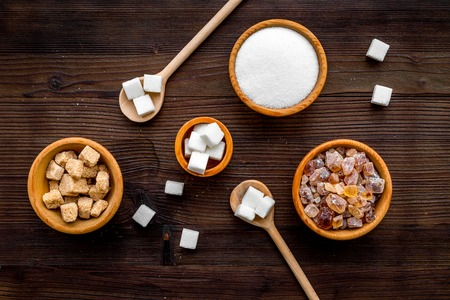 Sugar background on dark wooden table. Bowls with different kinds of sugar. Top view