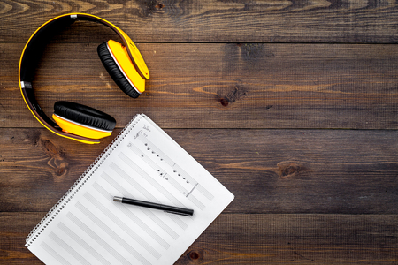 Work desk of modern composer. Music notes near headphones on dark wooden background top view copy space Stock Photo
