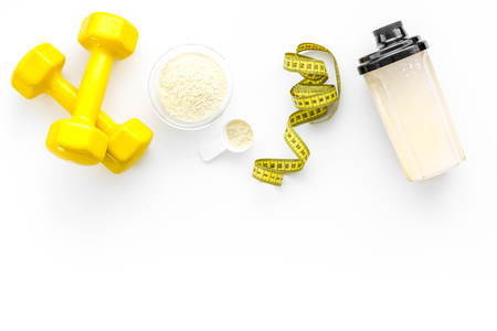 Nutrition for muscle growth. Scoop of protein near shaker and dumbbell on white background top view copy space
