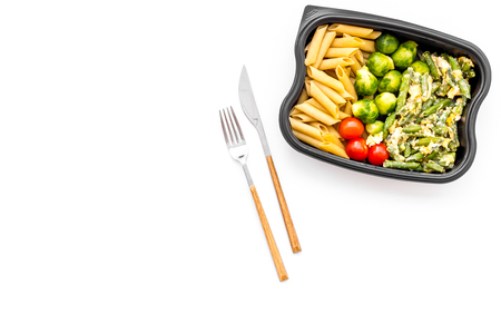 Gesundes und herzhaftes Mittagessen für Büroangestellte. Gemüse-Rosenkohl, Kirschtomaten, Schlagbohnen nähern sich Teigwaren im Plastikbehälter auf weißem Draufsicht-Kopienraum des Hintergrundes