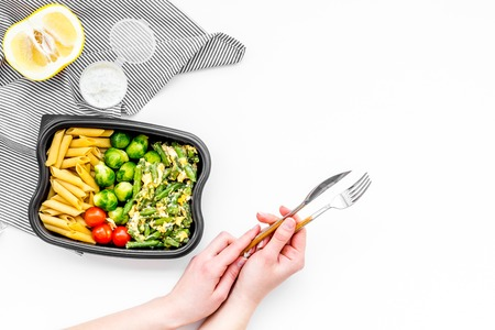Healthy and hearty lunch for office worker. Vegetables Brussels sprout, cherry tomatoes, knock beans near pasta in plastic container on white background top view.