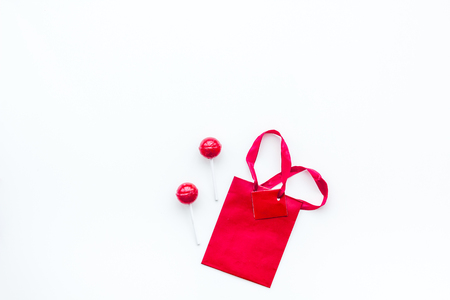 Gift concept. Sweets, paper bag for gift on white background top view.