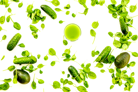 Green vegetables background with vegetable smoothies. Shiny bell pepper, cucumber, arugula salad, avocado on white background top view 스톡 콘텐츠