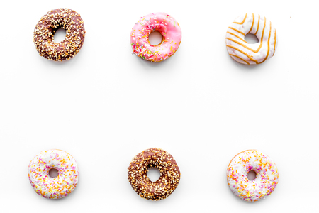 Donuts decorated icing and sprinkles on white background top view copy space pattern. Stock Photo