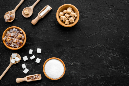 Brown and white sugar in bowls, scoop and spoon. Black background top view.
