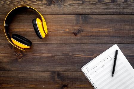 Work desk of modern composer. Music notes near headphones on dark wooden background top view.