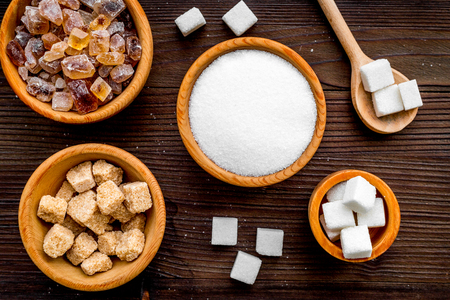 Sugar background on dark wooden table. Bowls with different kinds of sugar. Top view.