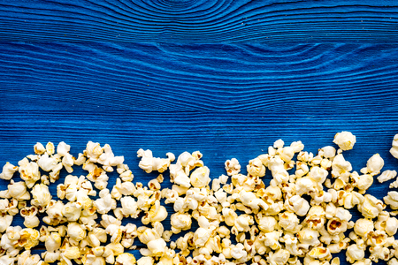 Popcorn background on blue top view copy space.