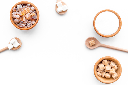 Brown and white sugar in bowls, scoop and spoon. White background top view.