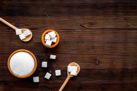 Types of sugar. White refined sugar. Granulated sugar and sugar cubes on dark wooden background top view.
