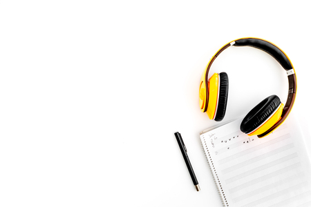 Work desk of modern composer. Music notes near headphones on white background top view.