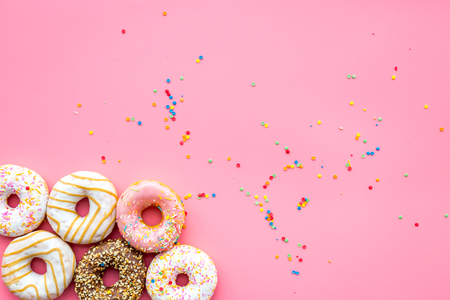 Donuts decorated icing and sprinkles on pink background top view copy space pattern