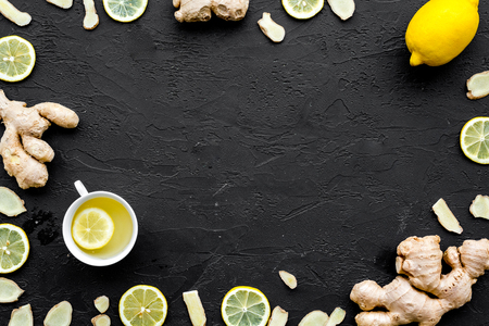 Ingredient for warming tea. Whole and sliced ginger roots, lemon on black background top view copy space Stock Photo
