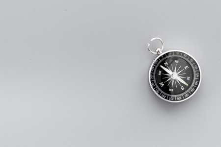 Compass on gray background top view copy space