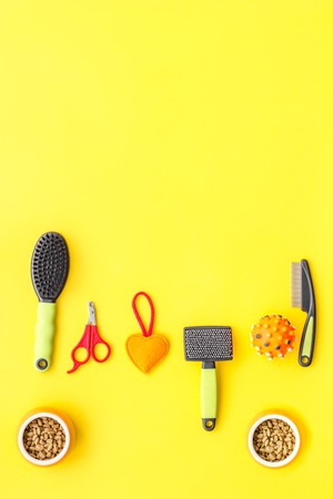 grooming equipment with brushes and toys for care and training pet yellow background top view mock up