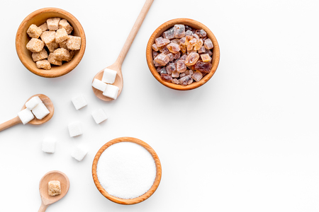 Brown and white sugar in bowls, scoop and spoon. Cane, refind, granulated, cubes, candy. White background top view copy space