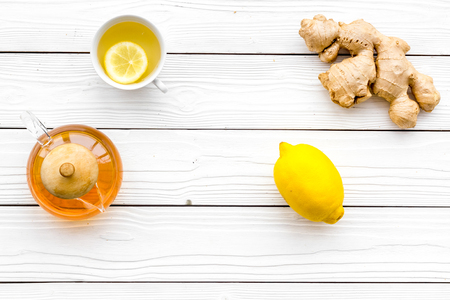 Warming tea with lemon and ginger. Cup, teapot, ginger root on white wooden background top view copy space