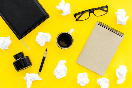 writer workplace with tools for work on yellow table background top view mockup