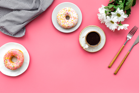 breakfast with coffee, donuts and flowers on pink background top view mockup
