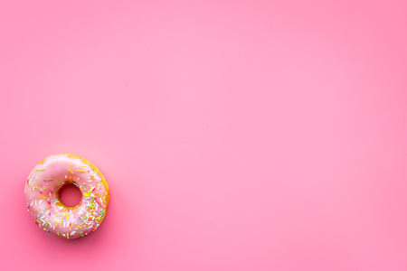 Sweet tasty snack. Glazed donut on pink background top view copy space