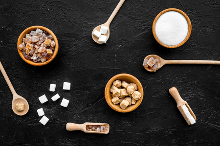 Sugar background on black. Bowls with different kinds of sugar. Top view Stock Photo